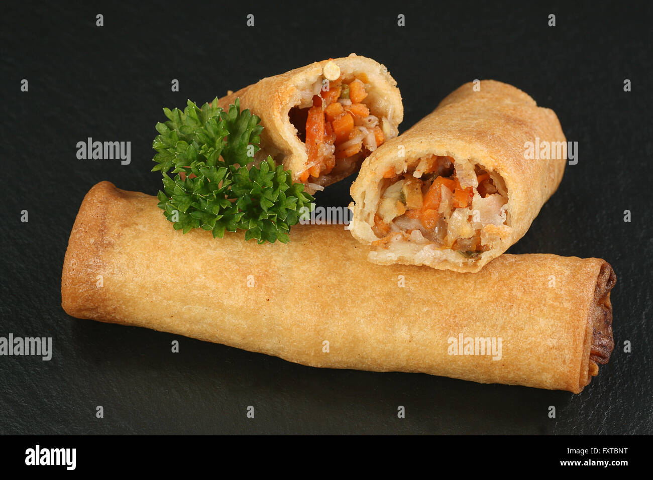 asian chinese vegetable spring rolls showing filling - Stock Image