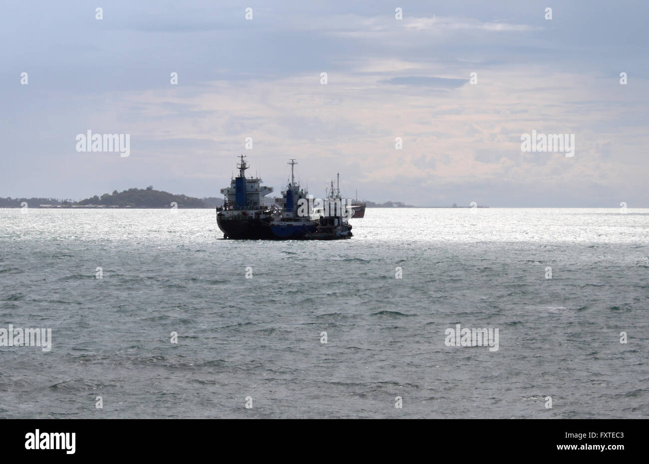 Seascape with three ships moored together in the ocean - Stock Image