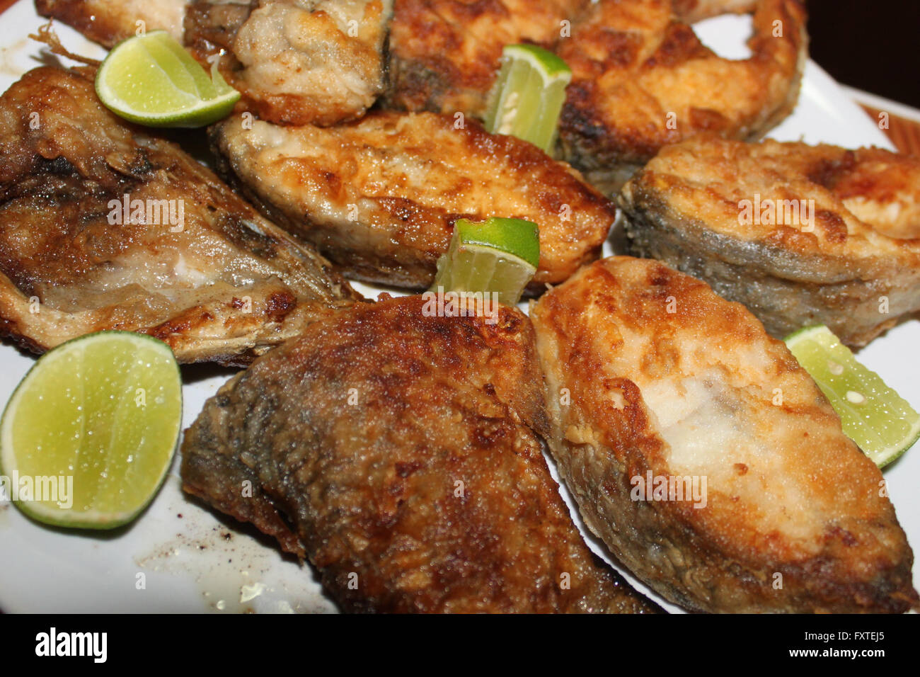 Ordinary fried fish in flour with slices of lime - Stock Image