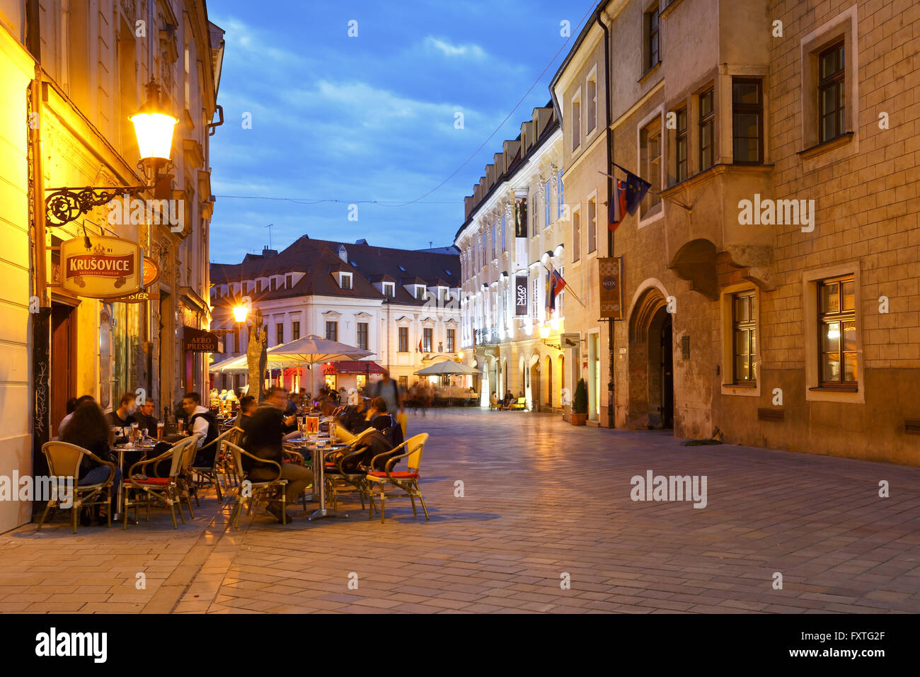 People in pubs in one of the main streets of the old town in Bratislava. - Stock Image