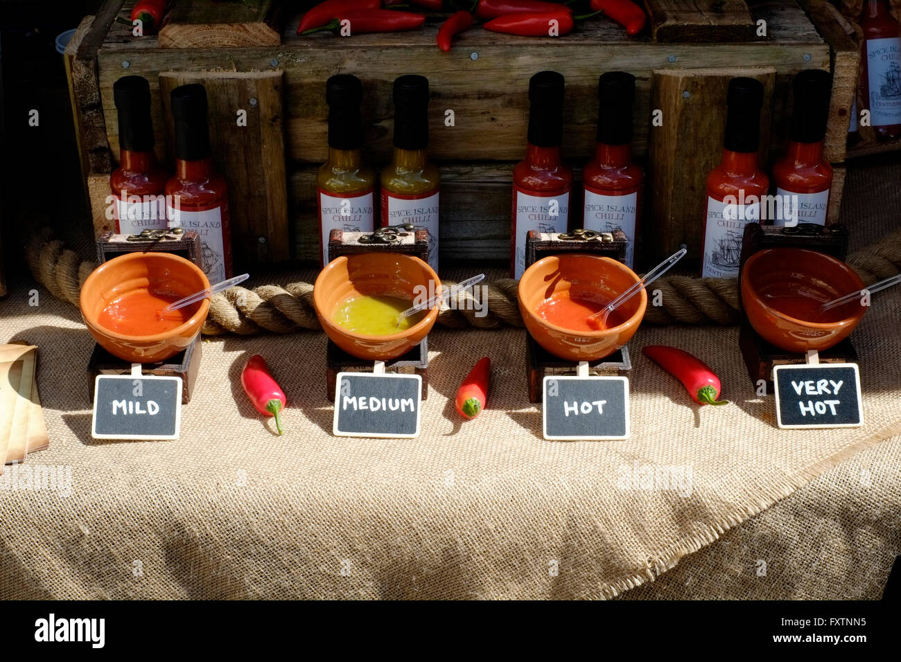 chilli sauces of various strengths for sale at a street market in southsea england uk - Stock Image