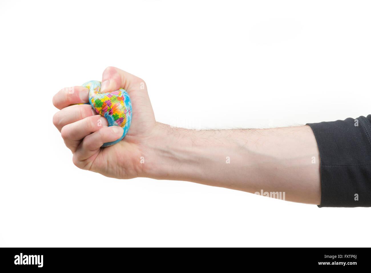 Hand squashing world globe - Stock Image