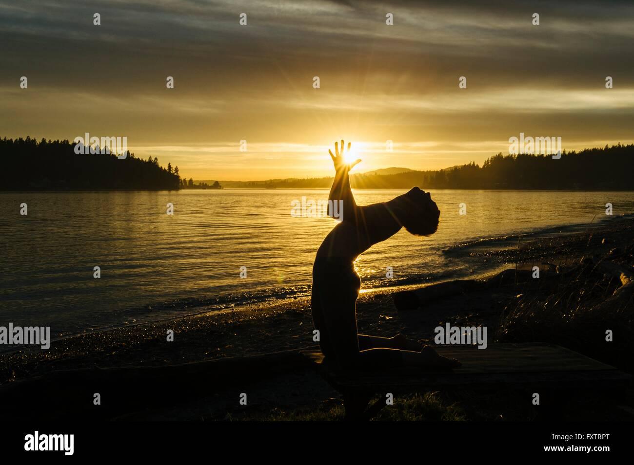 Woman practising yoga by lake at sunset - Stock Image