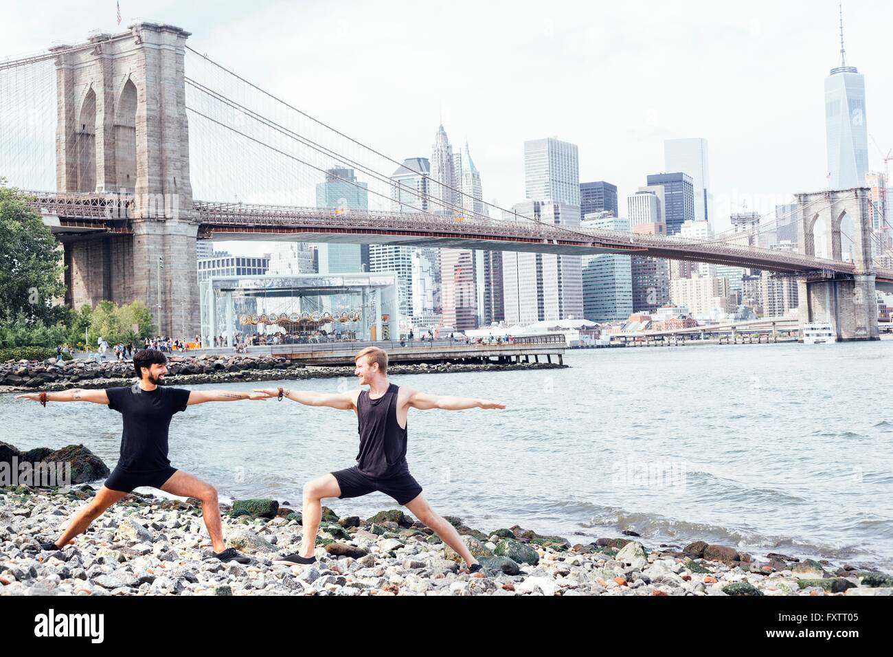 Two men practicing yoga on riverside in front of Brooklyn Bridge, New York, USA - Stock Image