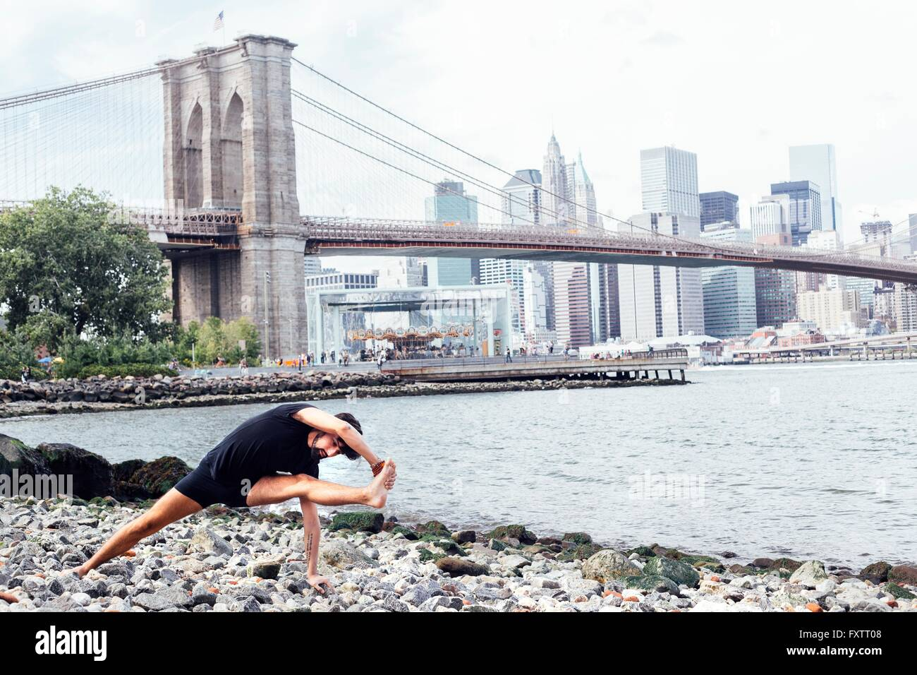 Young man practicing yoga on riverside in front of Brooklyn Bridge, New York, USA - Stock Image