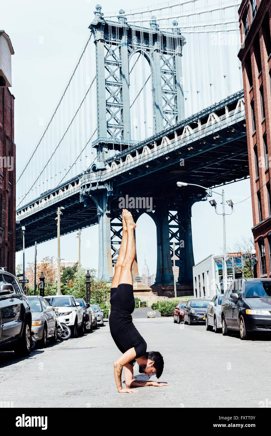 Young man doing yoga handstand in front of Manhattan Bridge, New York, USA Stock Photo