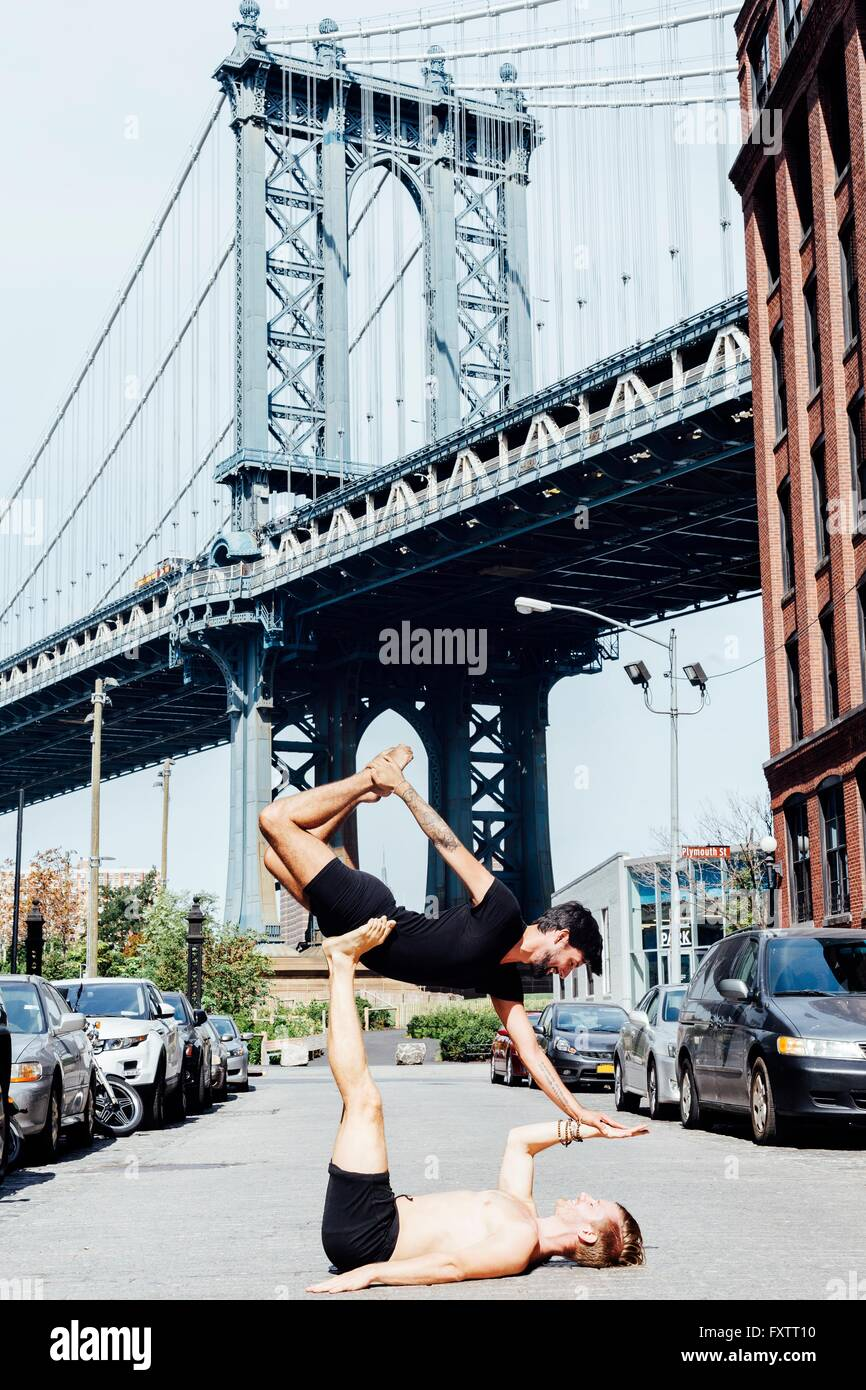 Man balancing on top of another in yoga position by Manhattan Bridge, New York, USA - Stock Image