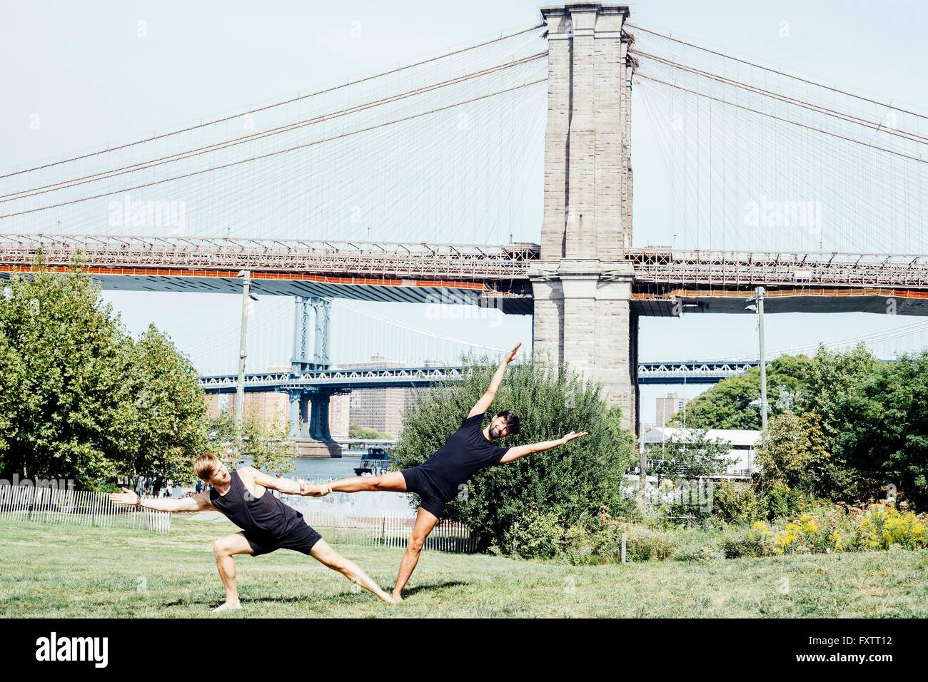 Two men leaning sideways in yoga foot hold position in front of Brooklyn Bridge, New York, USA - Stock Image