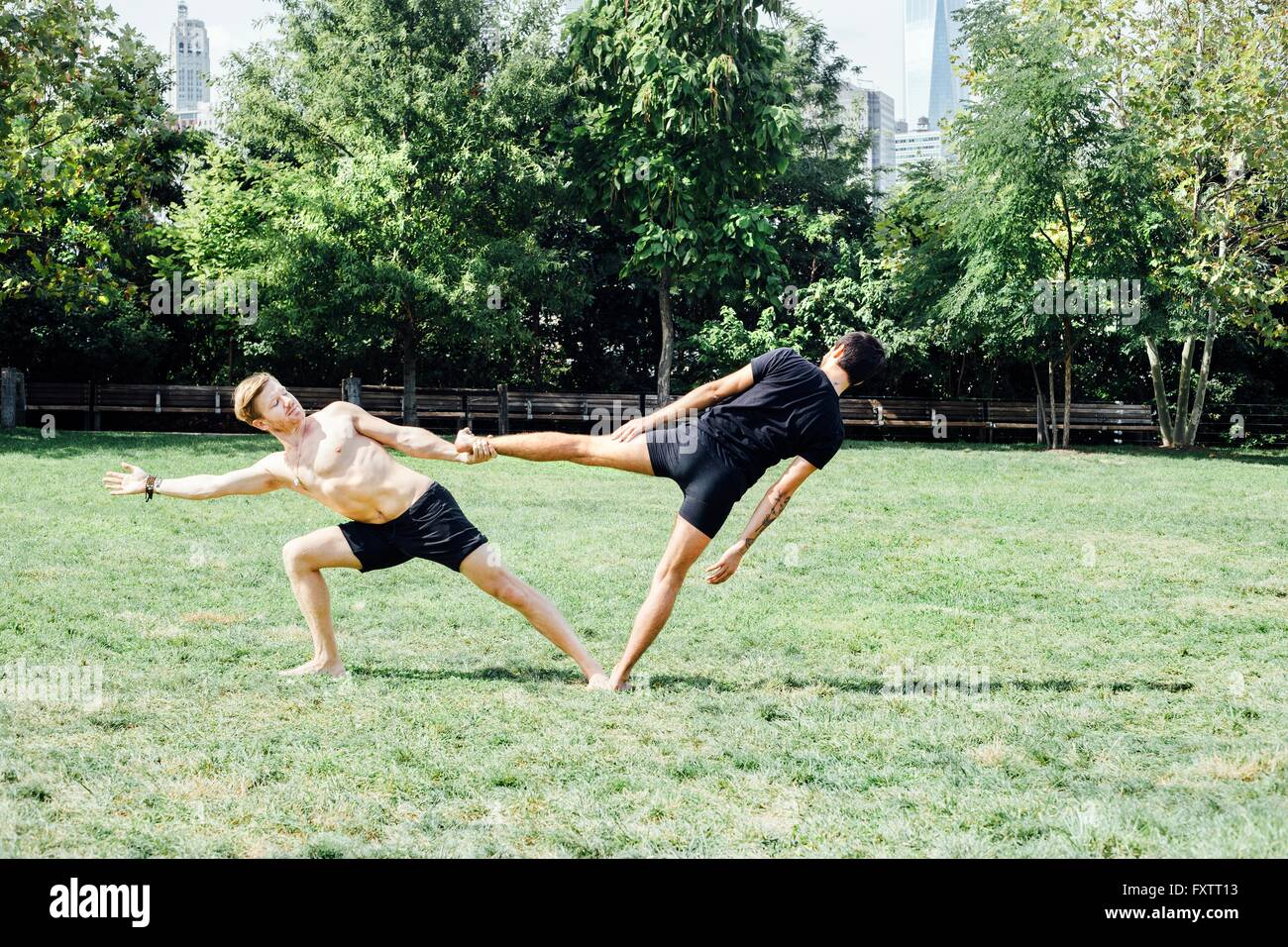 Two men leaning sideways in yoga foot hold position in park - Stock Image