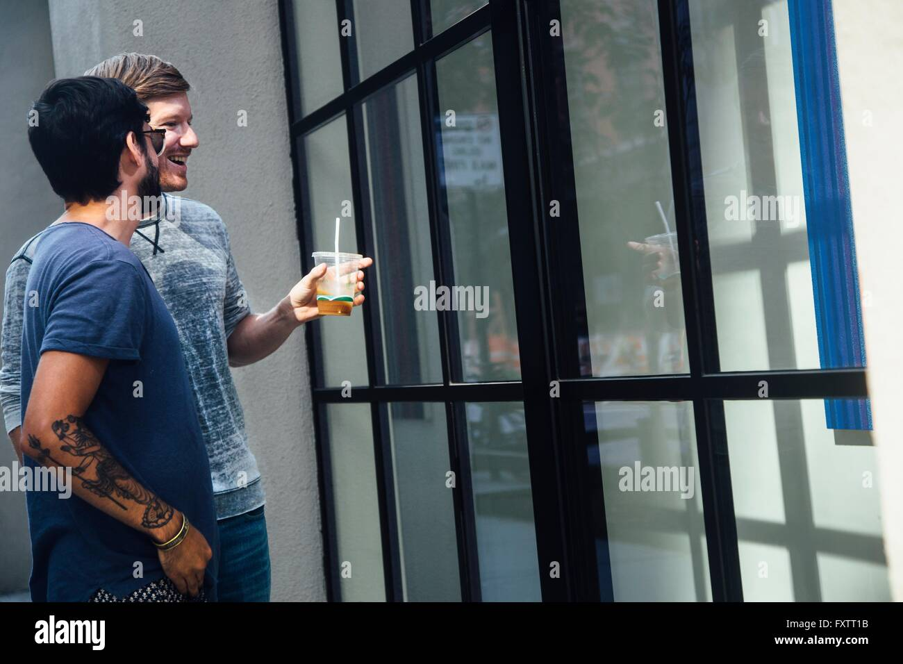 Male couple looking at city shop window Stock Photo