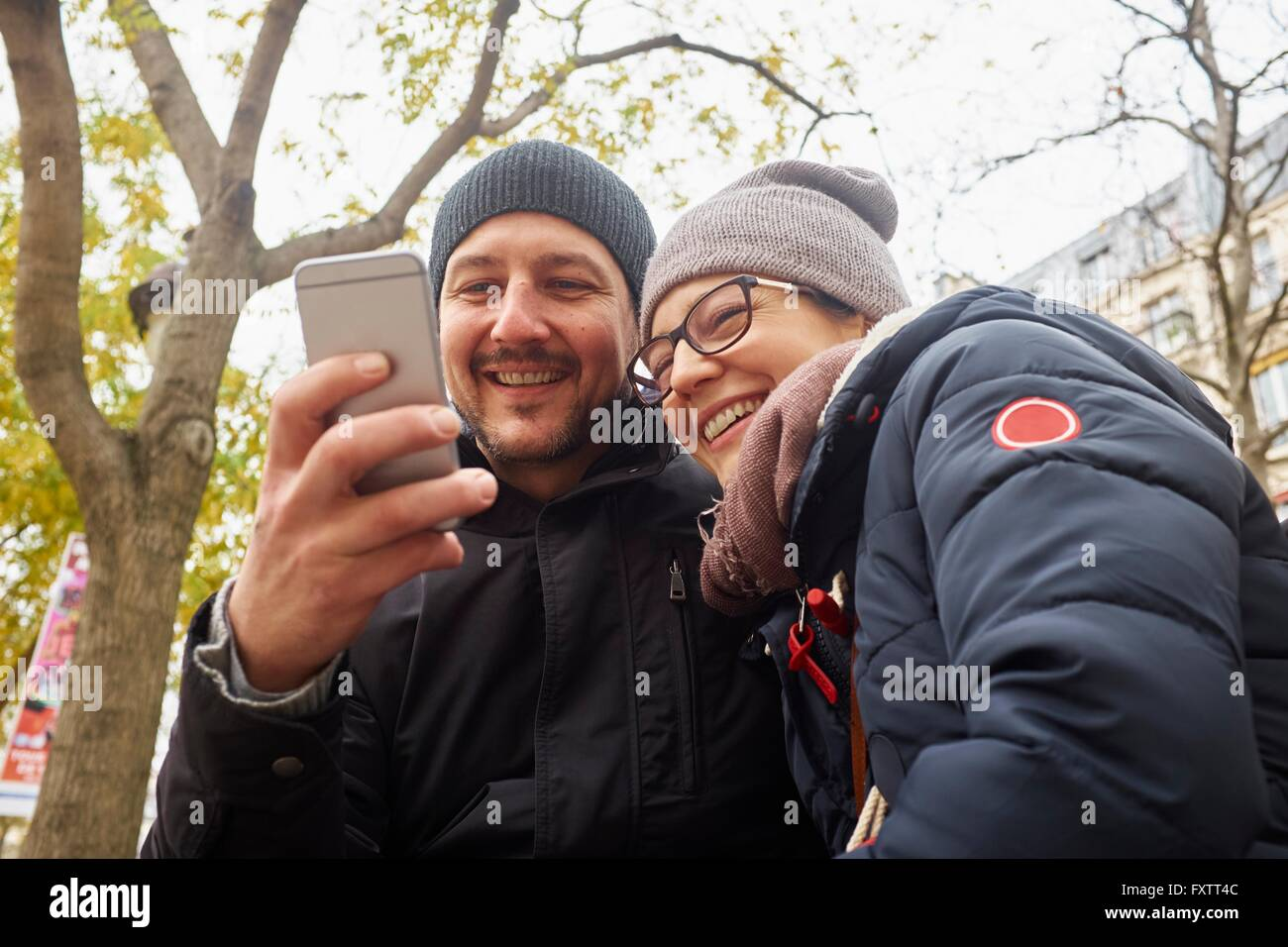 Couple wearing knit hats in park reading smartphone texts - Stock Image