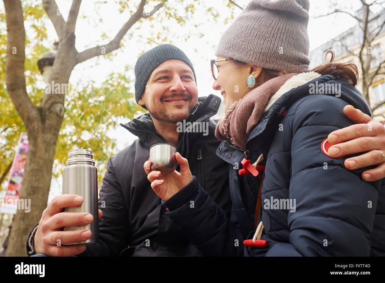 Couple wearing knit hats holding drinks flask in park - Stock Image