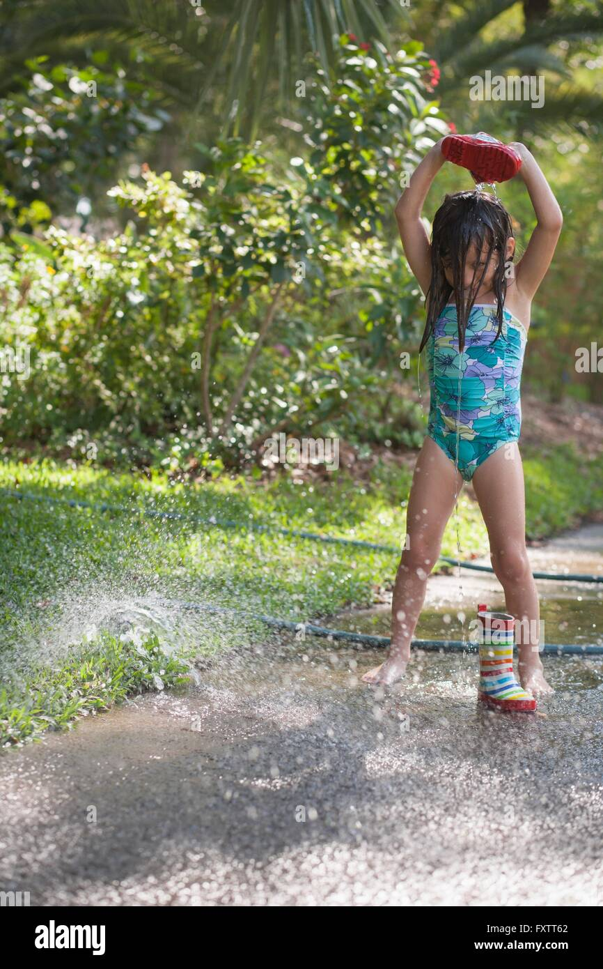 Girl pouring water from welly over head on sidewalk Stock Photo