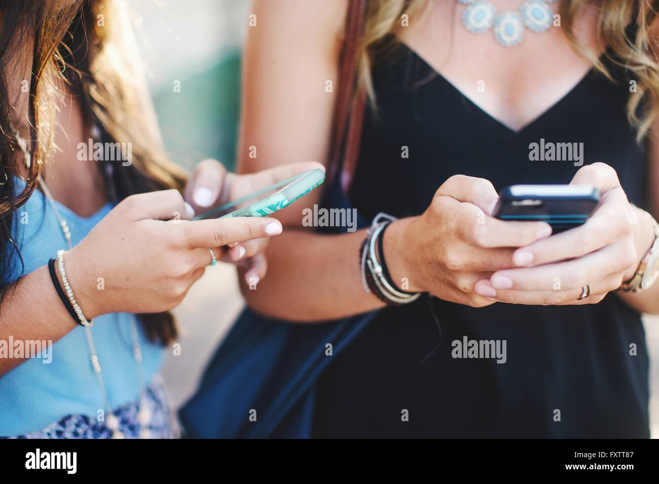 Cropped view of womens mid sections texting on smartphones - Stock Image