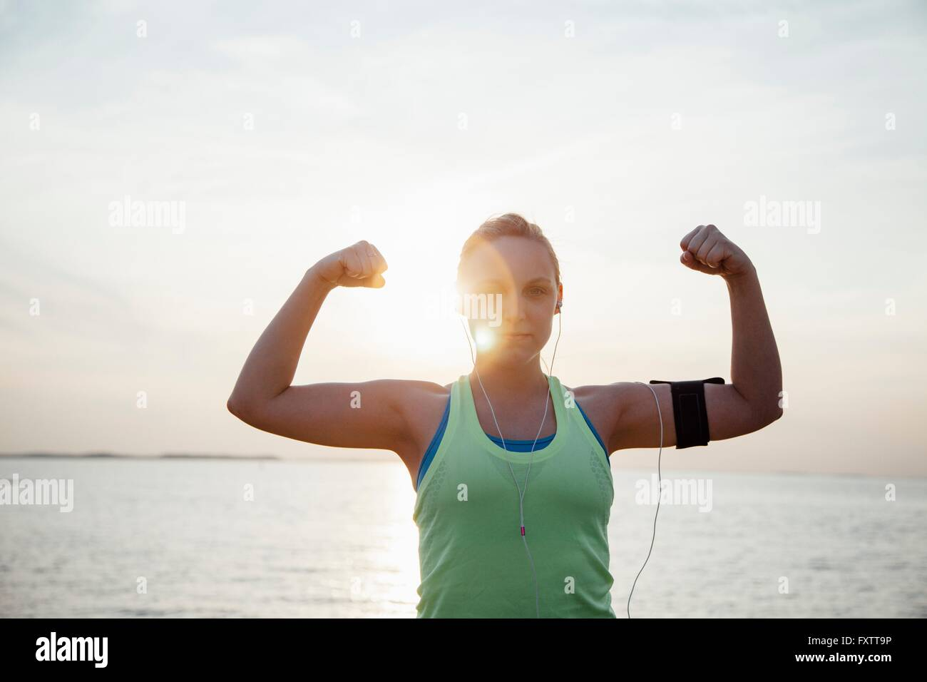 Woman wearing activity tracker, arms raised flexing muscles looking at camera - Stock Image