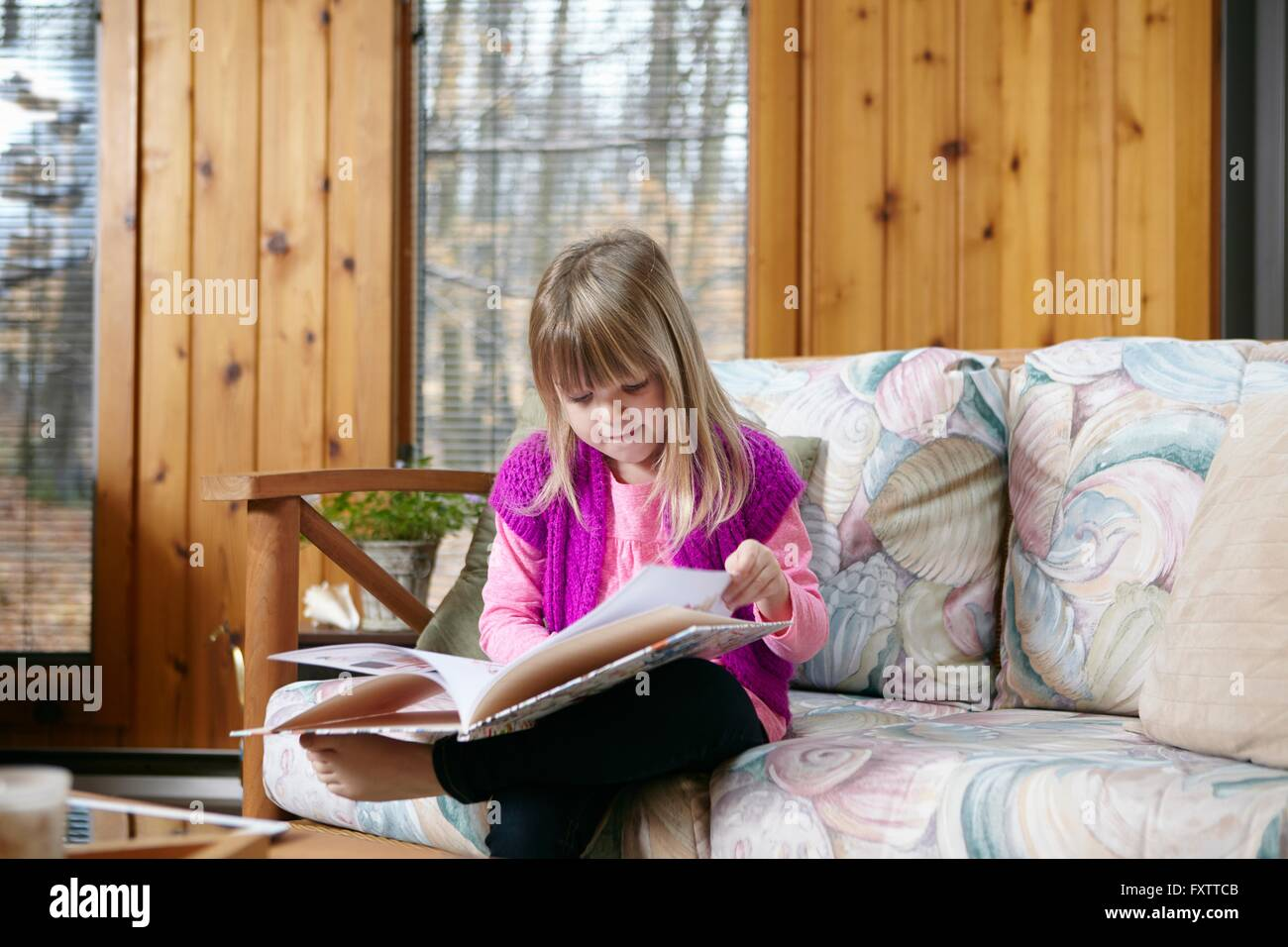 Girl sitting reading story book  on living room sofa - Stock Image