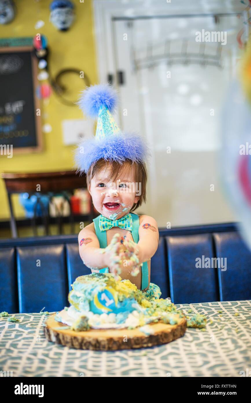 Baby boy wearing party hat smashing first birthday cake at table - Stock Image