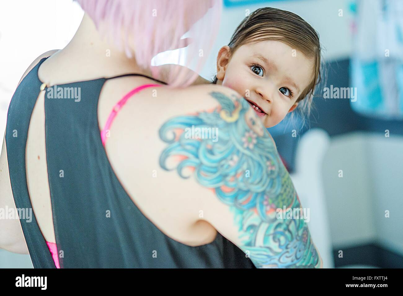 Portrait of baby boy peeking over his mothers tattoed shoulder - Stock Image