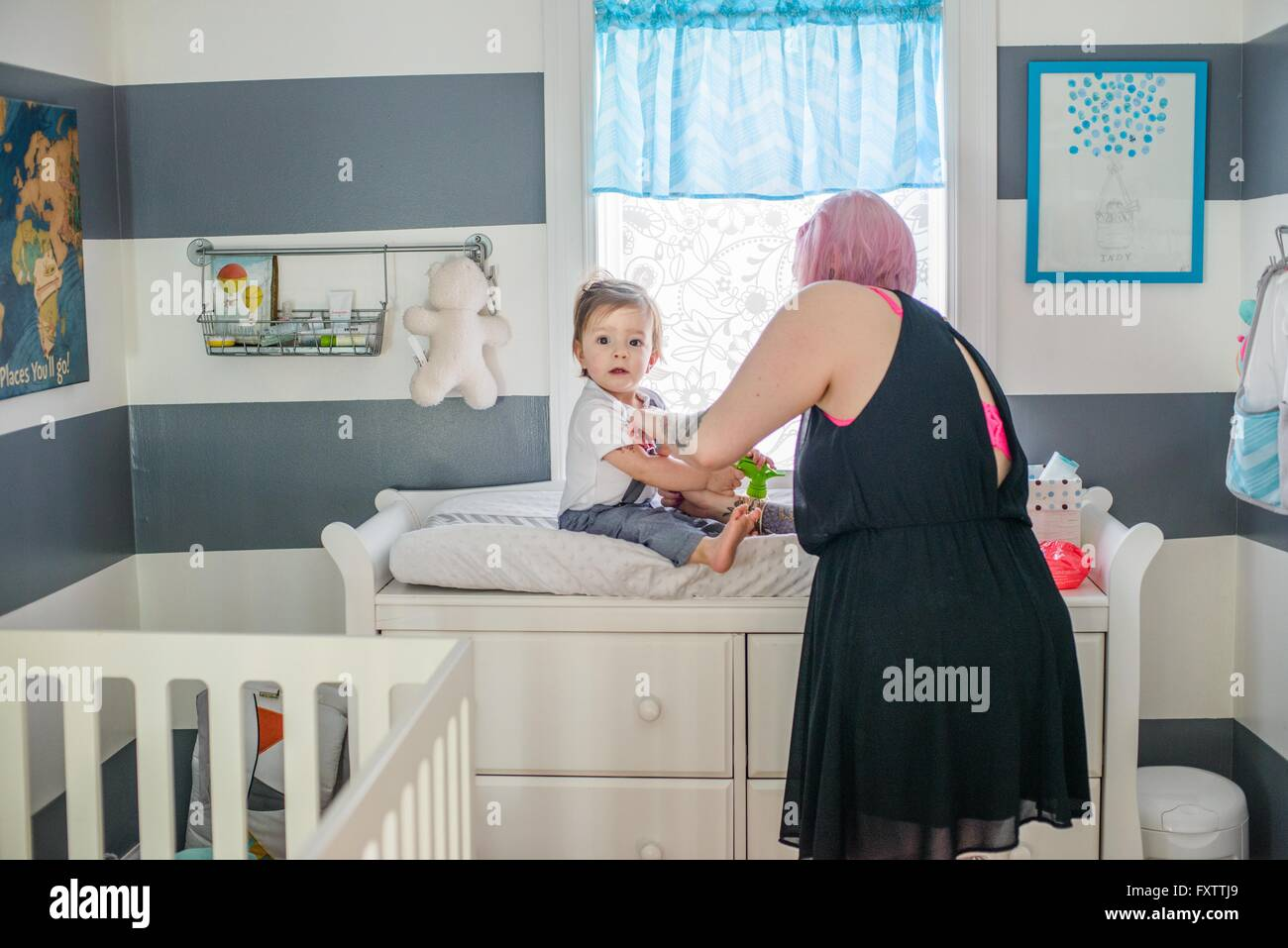 Mother getting baby son dressed on nursery day bed - Stock Image