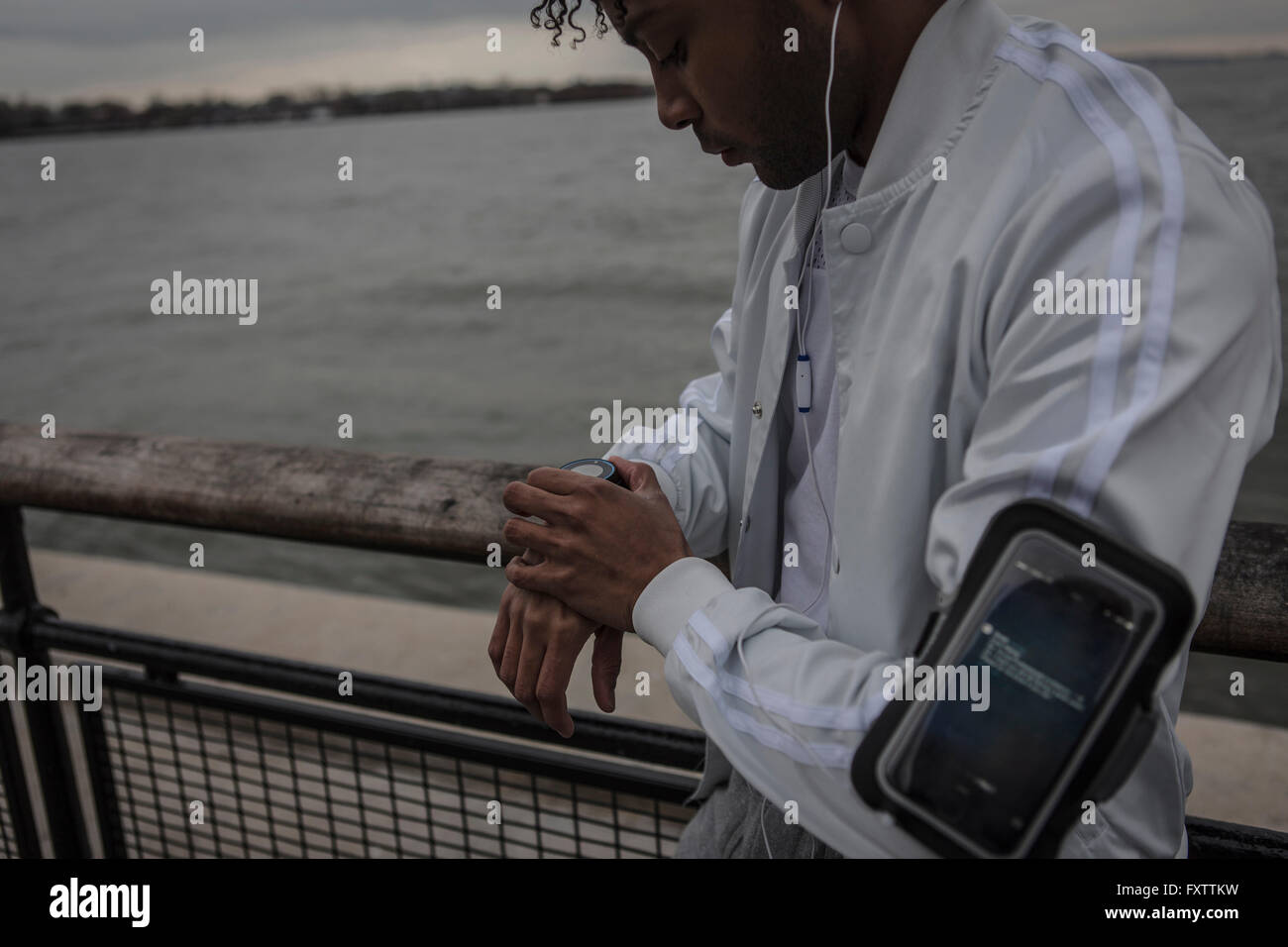 Young man training on riverside at dawn timing on smartwatch - Stock Image