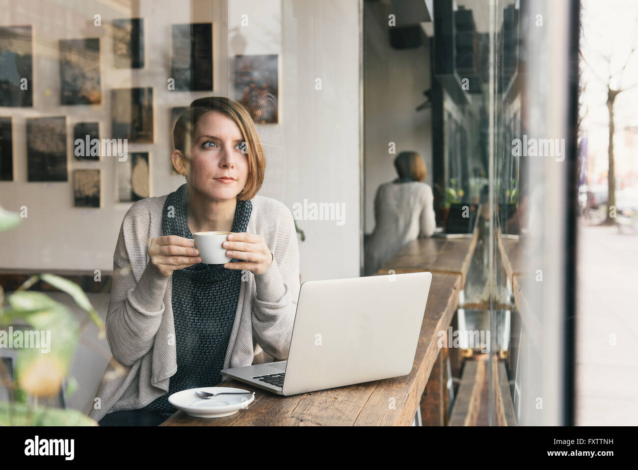 Woman Drinking Coffee Whilst Gazing From Coffee Shop