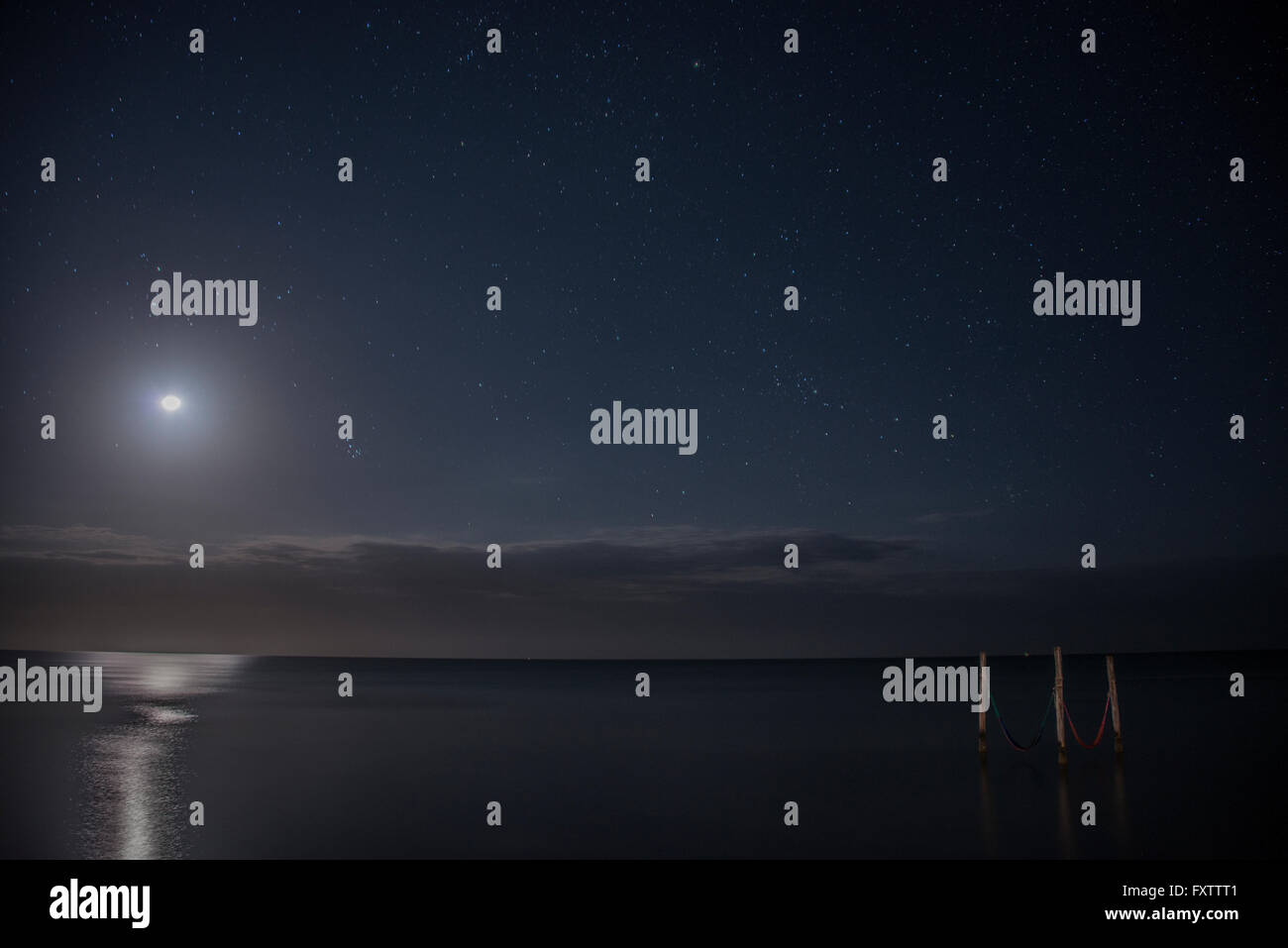 Starry sky and full moon illuminate iconic hammocks over waters, Isla Holbox, Mexico - Stock Image