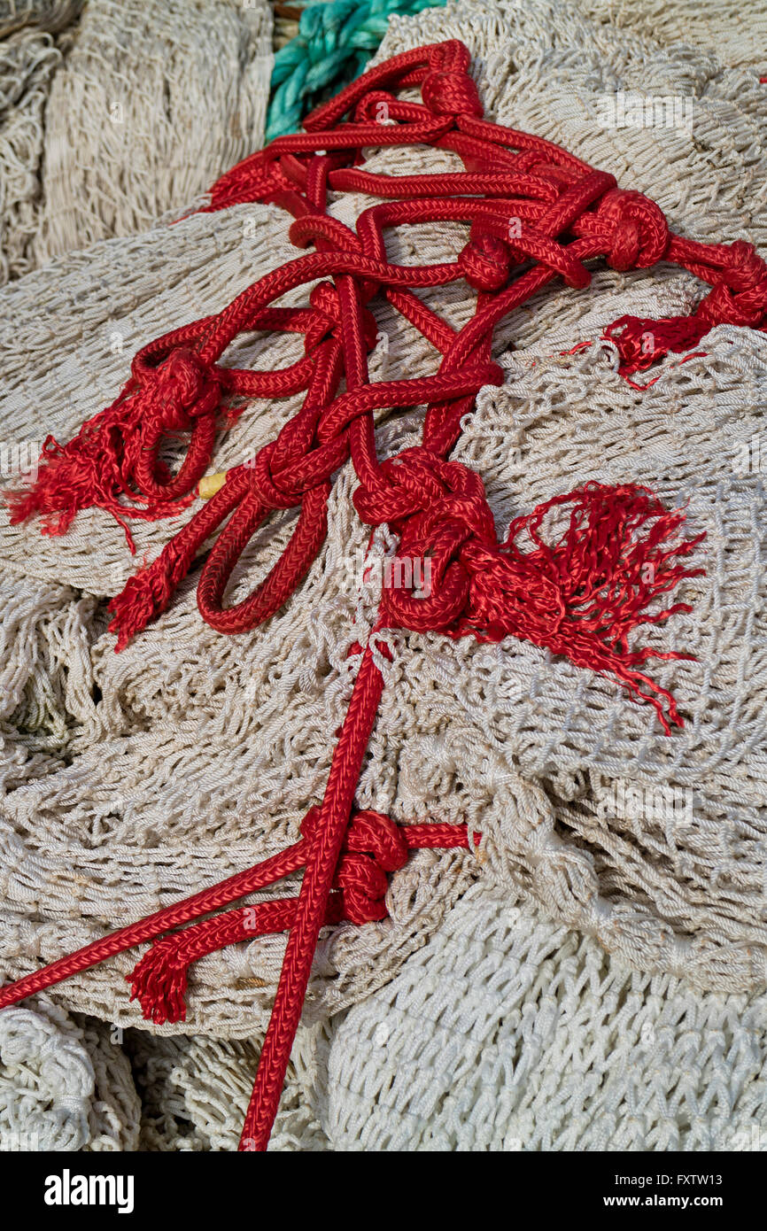Pile of fishing nets and red chord - Stock Image