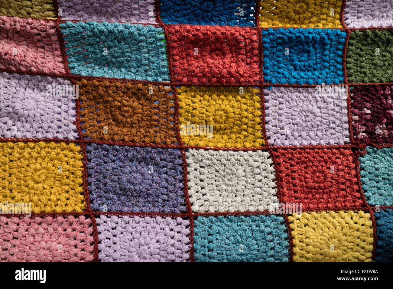 Colorful handmade crochet blanket on the market - Stock Image