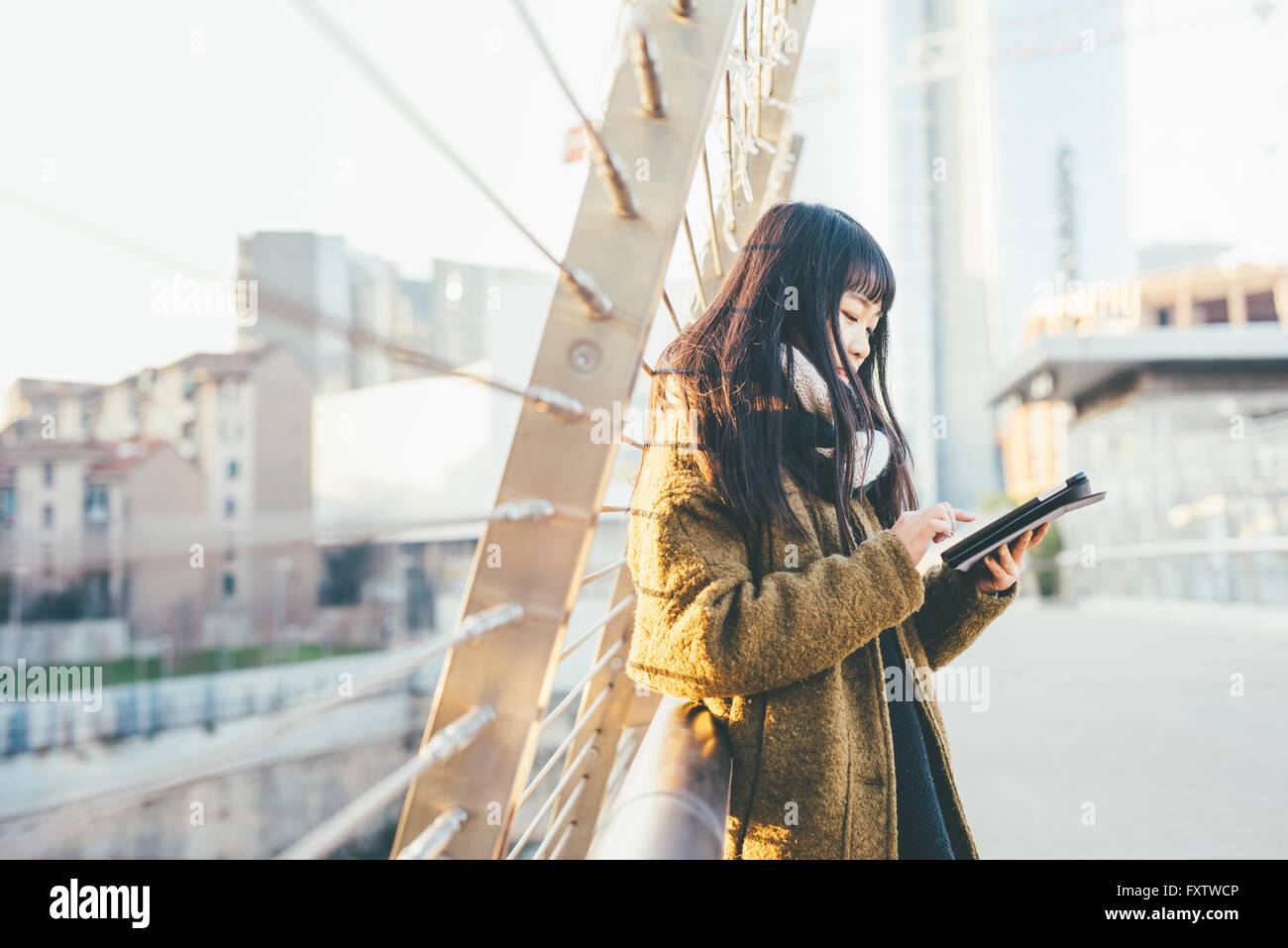 Half length of young beautiful asiatic woman holding a tablet, looking downward and tapping the screen - social - Stock Image