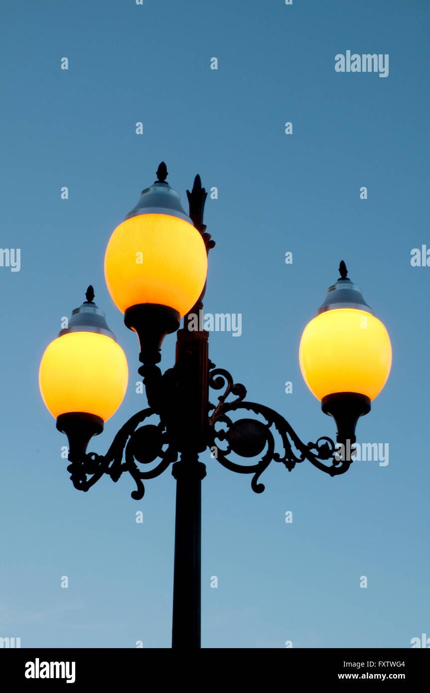 Lit up sreet lamp at evening. - Stock Image