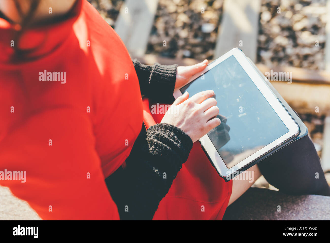 Rear view close up of young beautiful woman holding a tablet, tapping the screen - technology, social network, communication - Stock Image