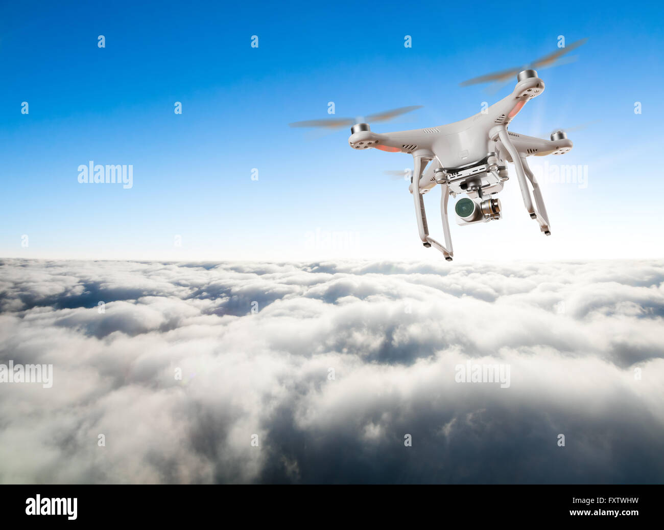 Drone for industrial works flying above clouds. Concept of pottential danger of aircraft collision - Stock Image