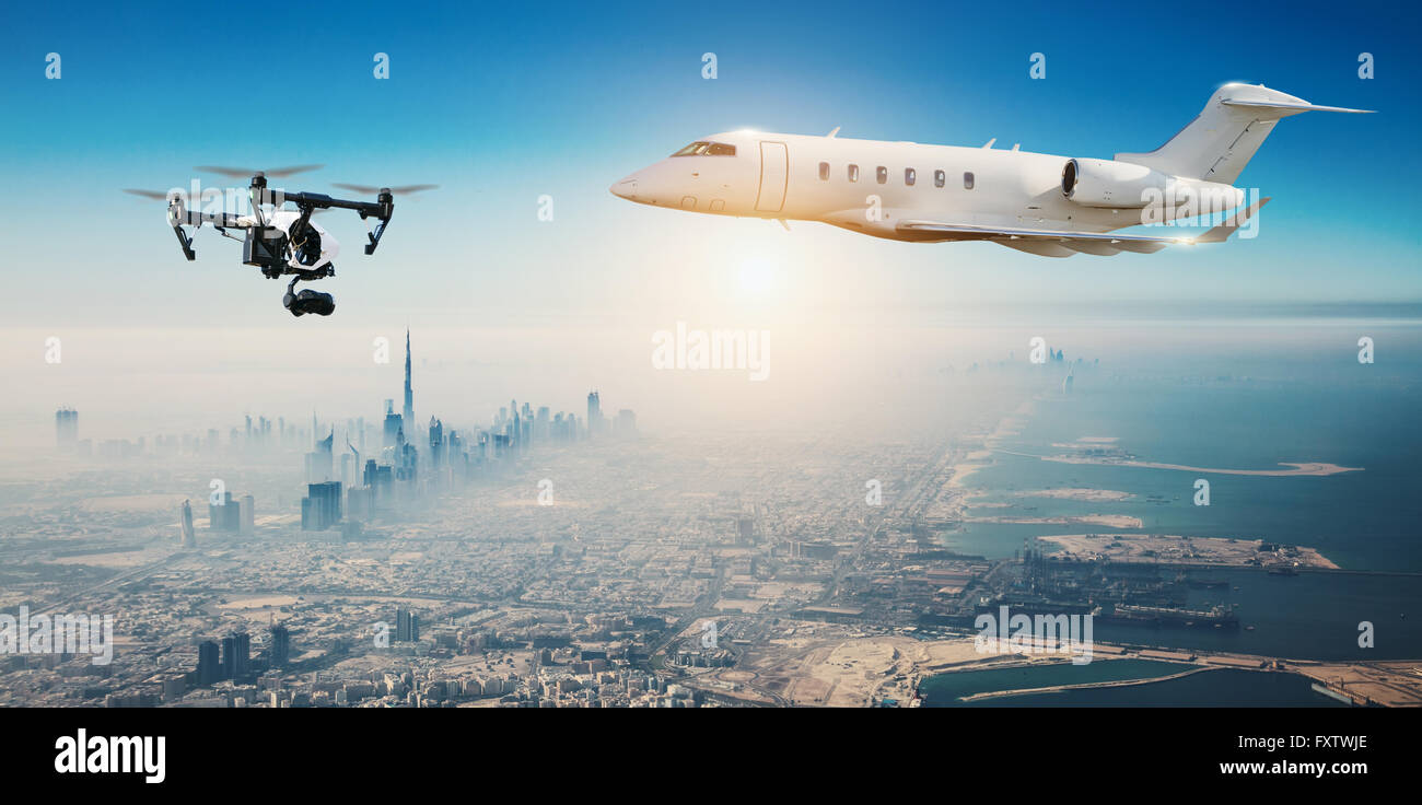 Drone potentially being hit by commercial airplane above modern city panorama. Concept of aircraft accident. Thread - Stock Image