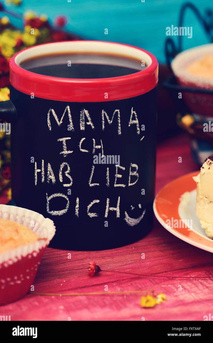 the sentence mama ich hab lieb dich, I love you mom in german handwritten with chalk in a black mug with coffee, - Stock Image