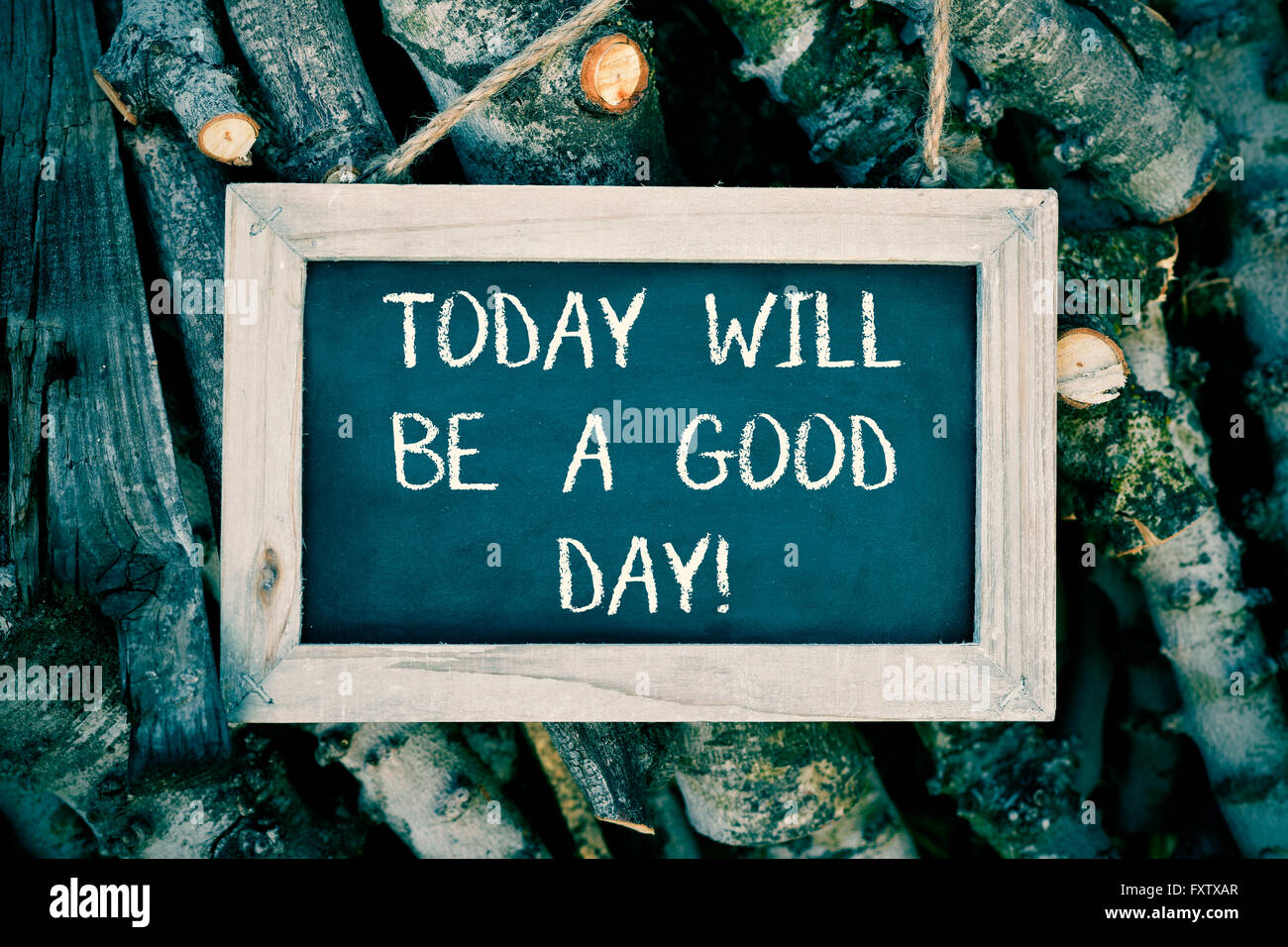 an aged chalkboard with the text today will be a good day placed on a pile of logs - Stock Image