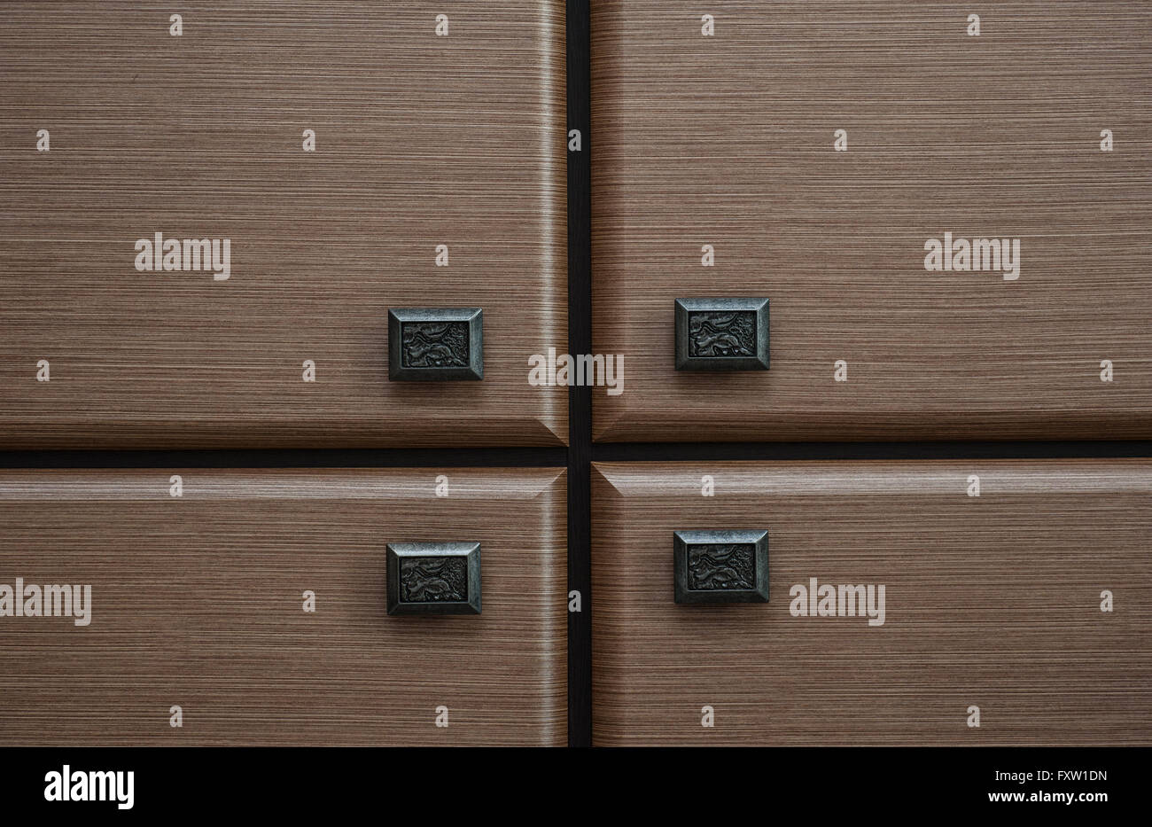 detail of four wooden drawers with metal handles - Stock Image