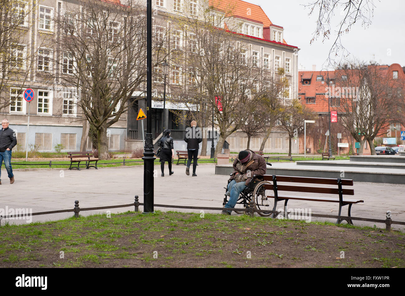 Homeless hunched invalid man on the wheelchair, sleeping outside in the park, cold spring day in Gdansk, Pomeranian - Stock Image