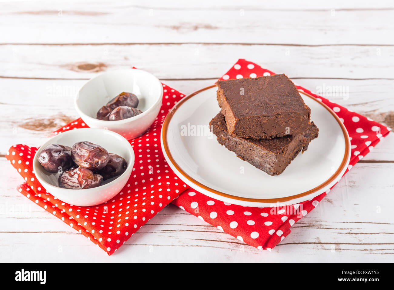 Healthy gluten free Paleo style brownies made with sweet potato, dates and almond flour on a white plate - Stock Image