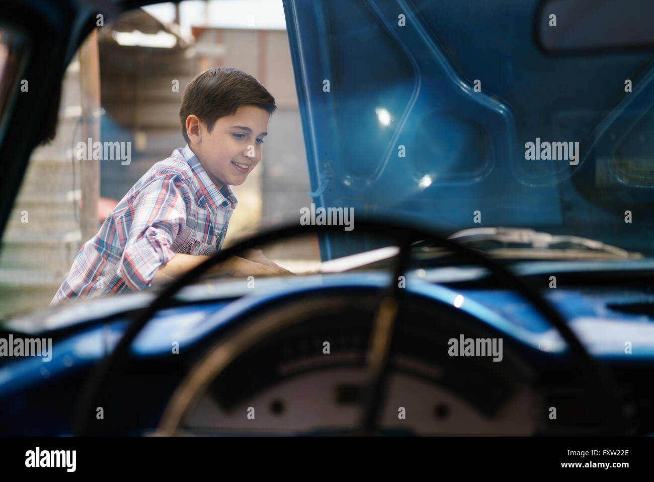 Preteen child looking at the engine of a vintage car from the 60s. He is amazed and excited. The boy smiles happy - Stock Image