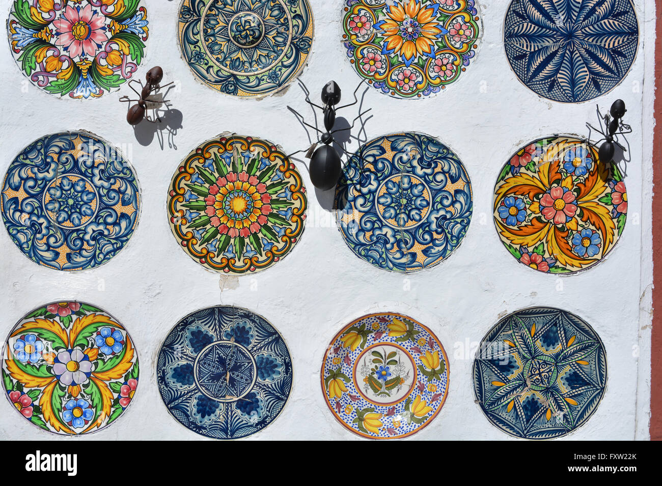 Display of hand-painted ceramic plates and metal ants decorating the wall of a souvenir shop Gata de Gorgos Valencia Spain. & Display of hand-painted ceramic plates and metal ants decorating the ...
