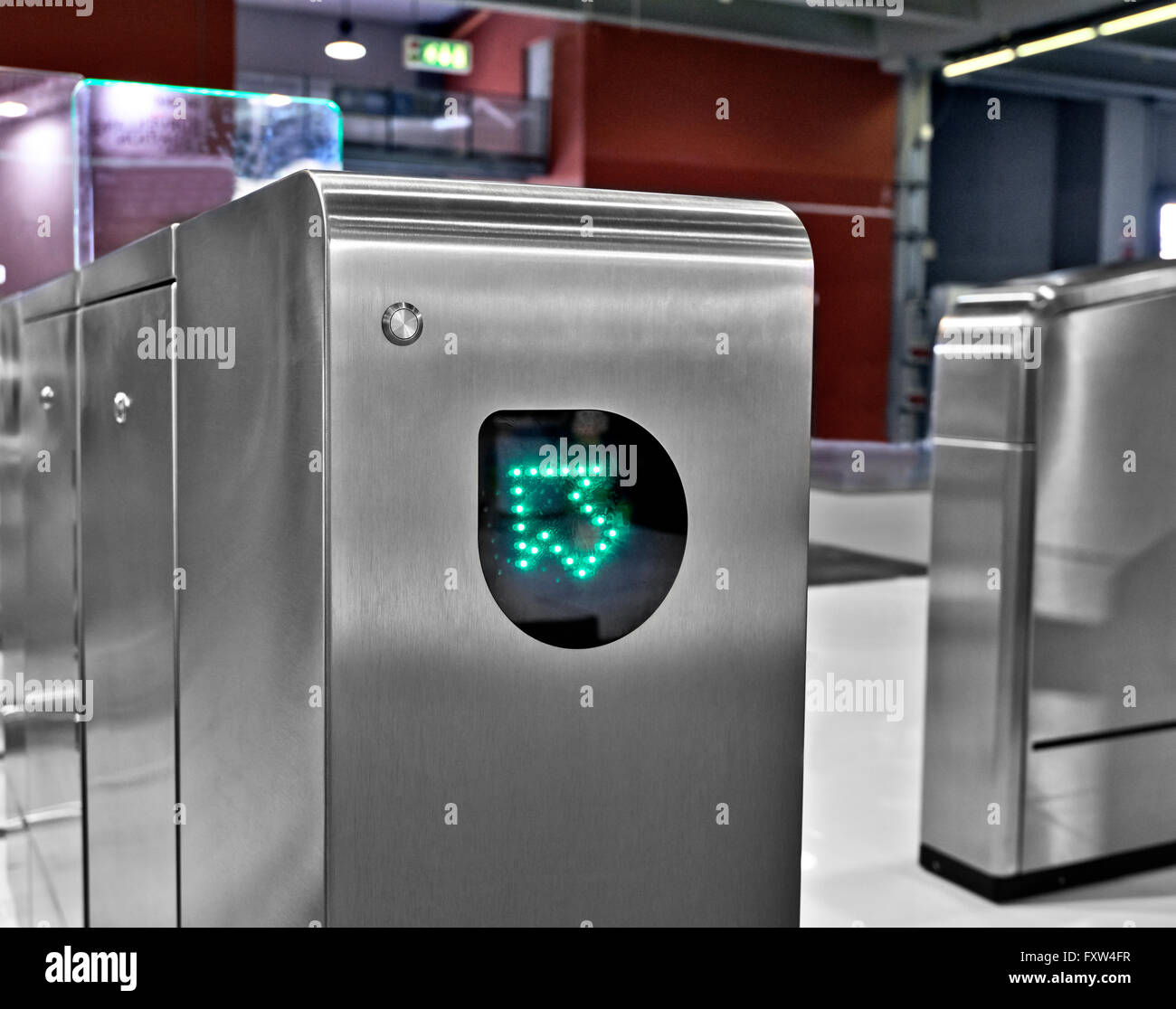Entrance wicket of a subway station with green arrow - Stock Image