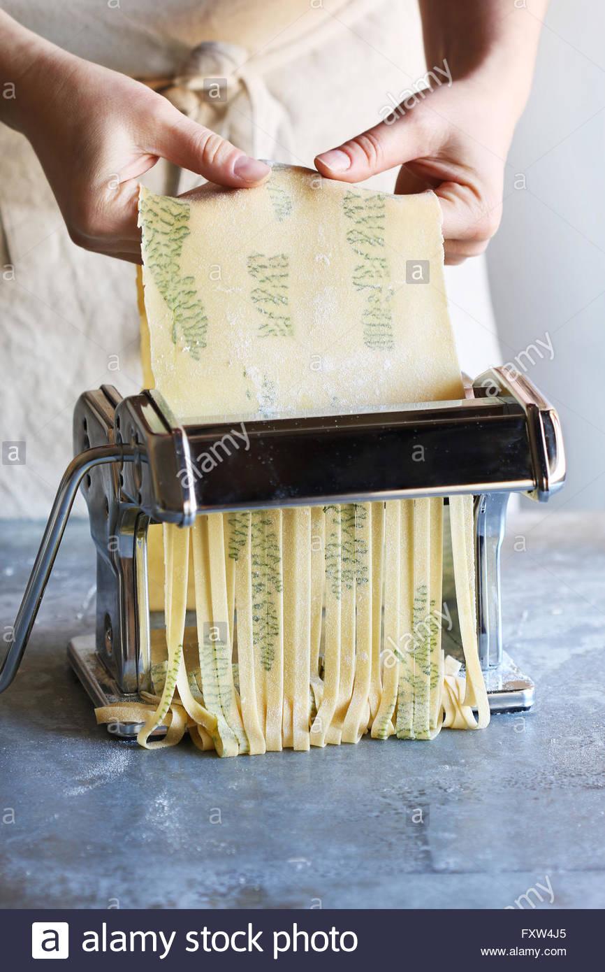 Making herb pasta tagliatelle with pasta machine. - Stock Image