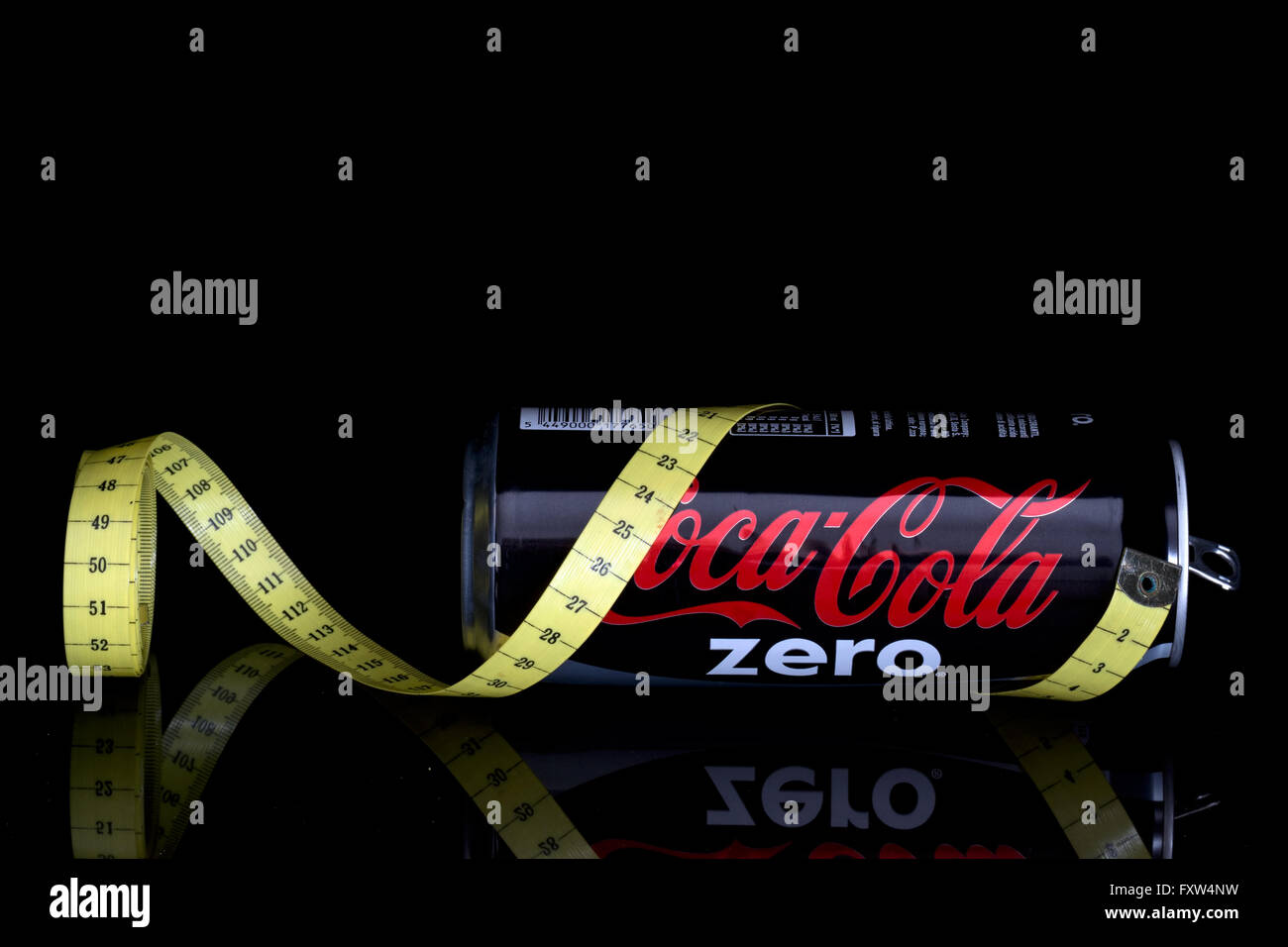 Low calorie Coca cola fizzy drink with tape measure. Sugar free. On black. - Stock Image