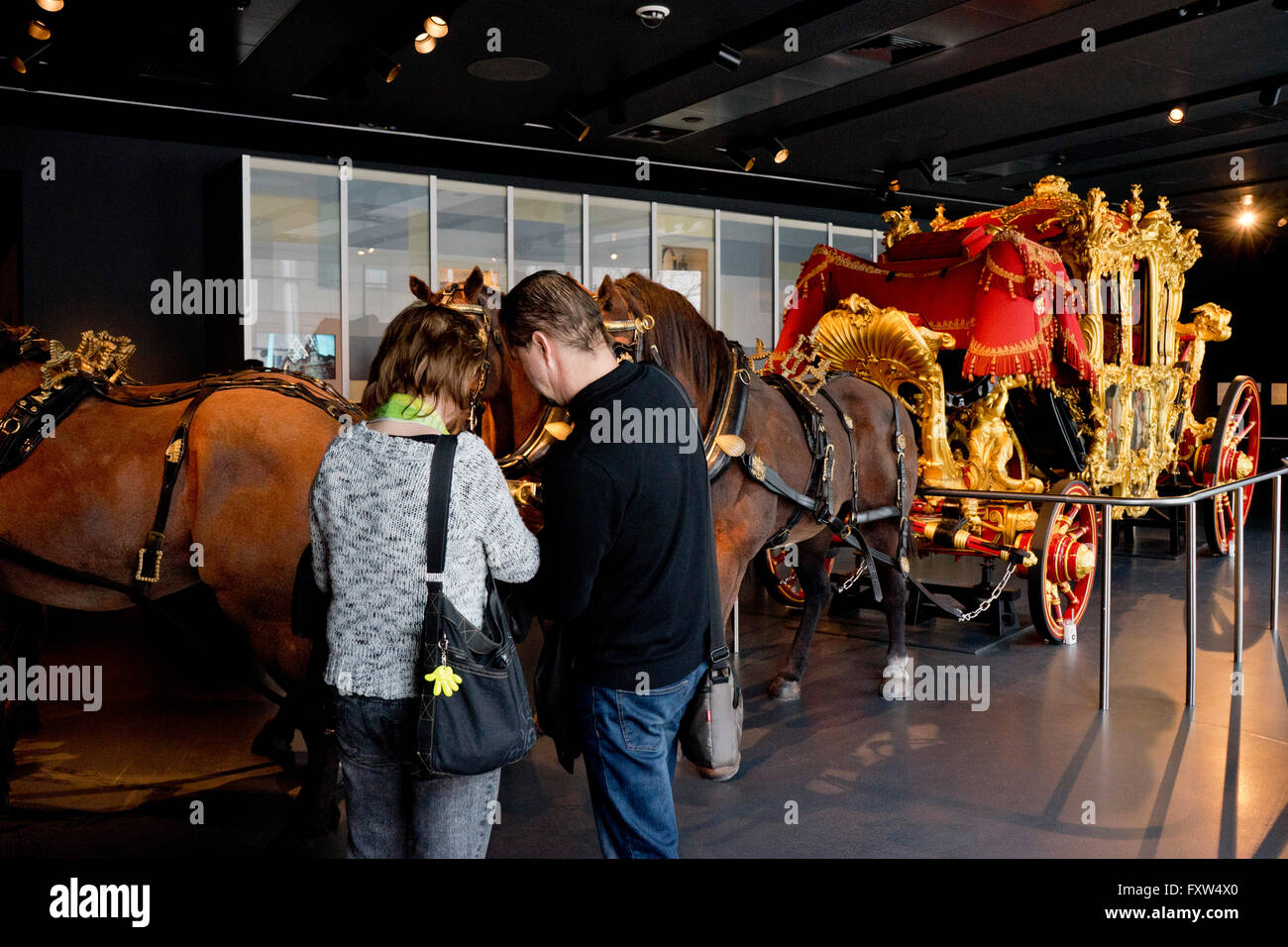 Visitors to the Museum of London inspect the Lord Mayor carriage. London, England, UK - Stock Image