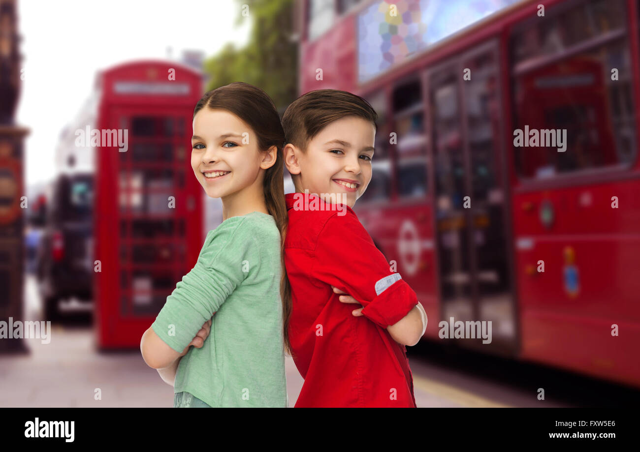 happy boy and girl standing over london city - Stock Image