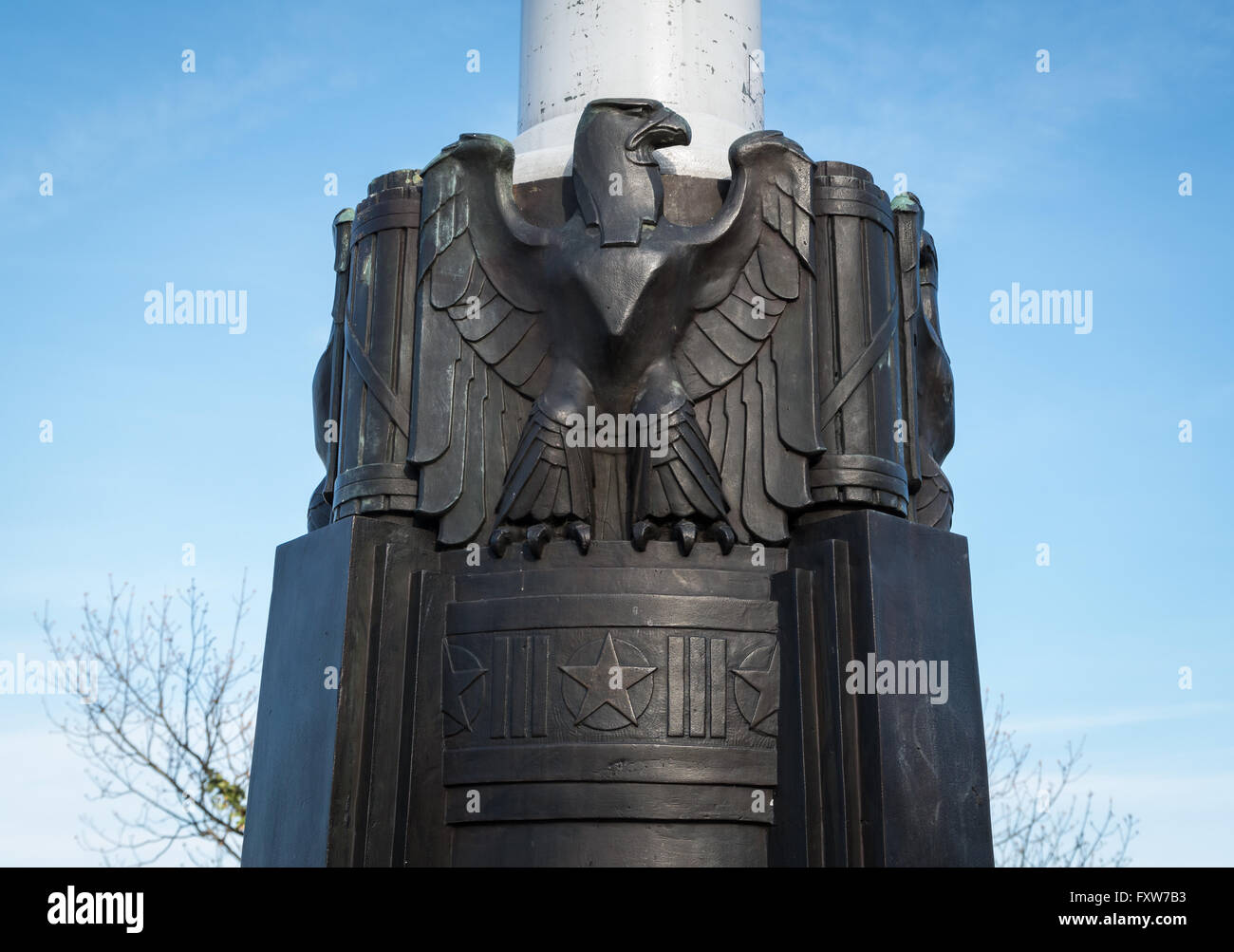 American Bald Eagle emblem cast in bronze at the base of a flagstaff pedestal with stars and stripes symbols in - Stock Image