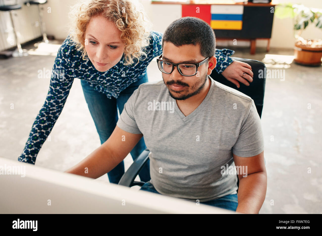 Portrait of two young graphic designers working on computer in office. Male and woman designers looking at computer - Stock Image