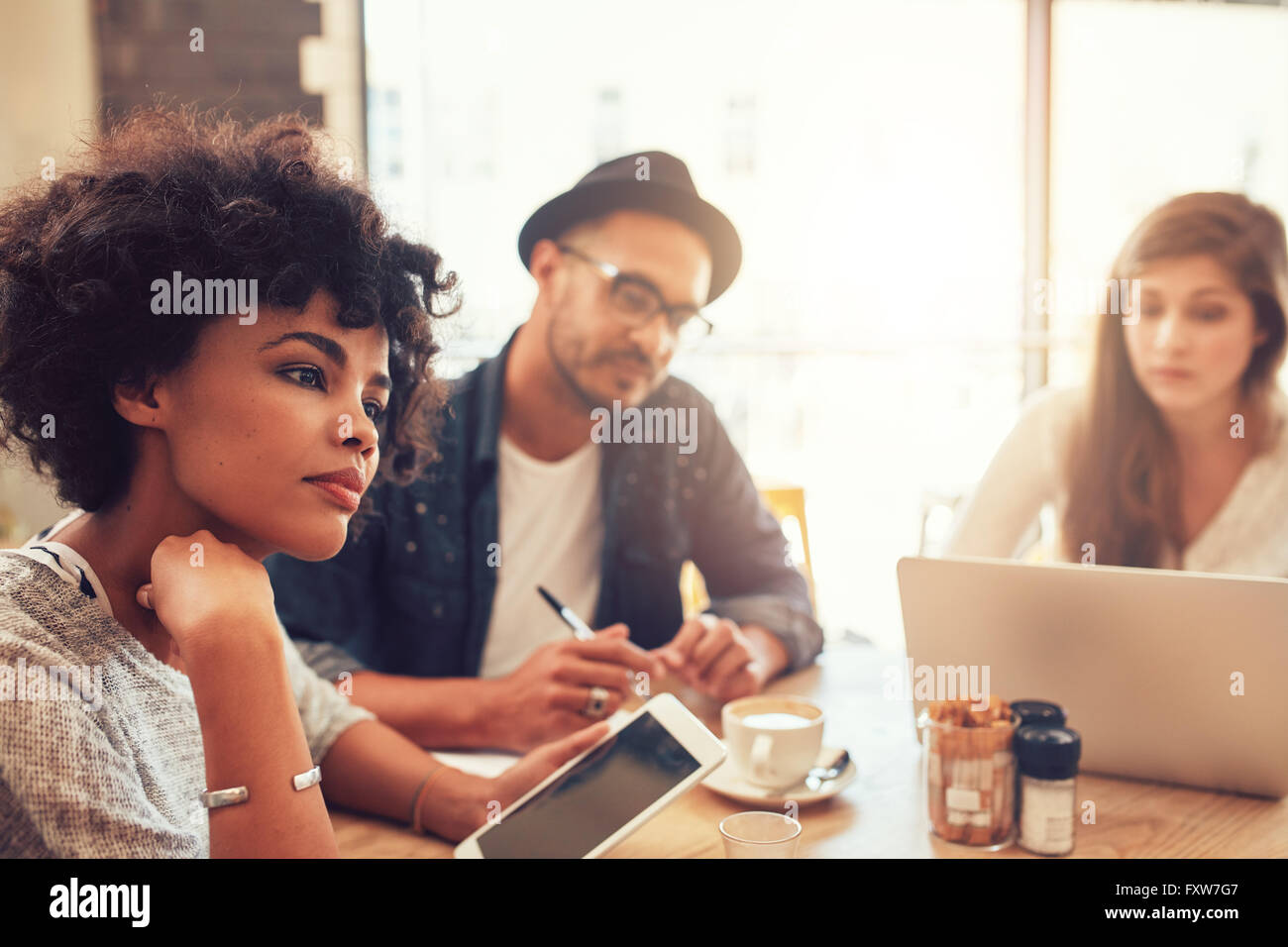 Close up portrait of young african woman with digital tablet and people in background at a cafe table. Young people - Stock Image