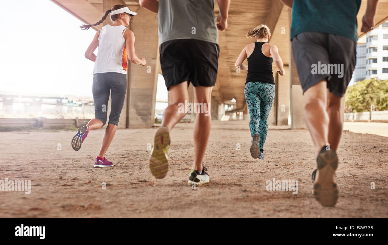 Rear view of young people running under the bridge in the city. Low angle shot of group of young men and women jogging - Stock Image