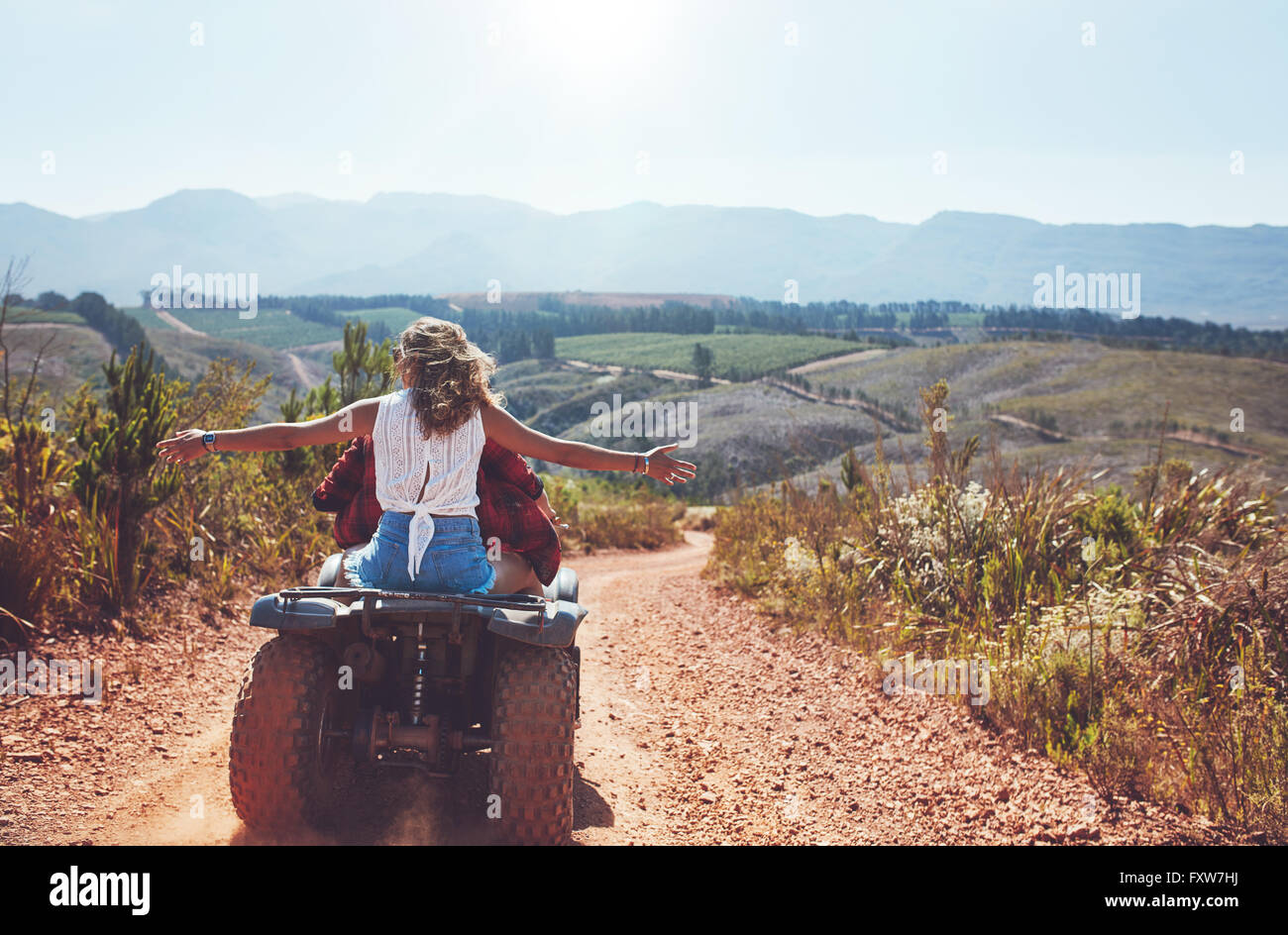 Portrait of young couple in nature on a off road vehicle. Young man and woman having fun on a quad bike in countryside. - Stock Image